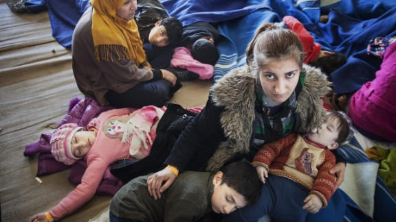 A Syrian refugee mother comforts her children, after being rescued from a fishing boat carrying 219 people.