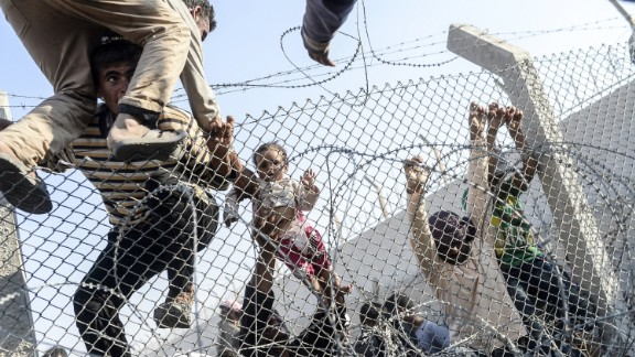 A Syrian child fleeing the war gets lifted over fences to enter Turkish territory illegally near a border crossing at Akcakale, Turkey, on June 14, 2015.