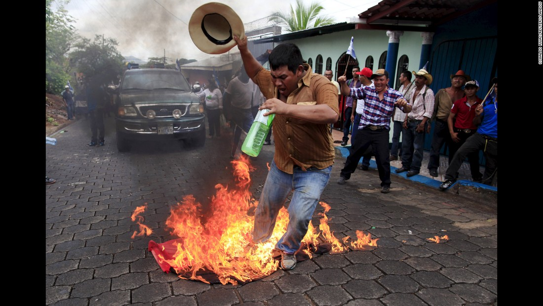 A man in Juigalpa, Nicaragua, burns the flag of the Sandinista National Liberation Front while protesting the construction of the Nicaragua Grand Canal on Saturday, June 13.