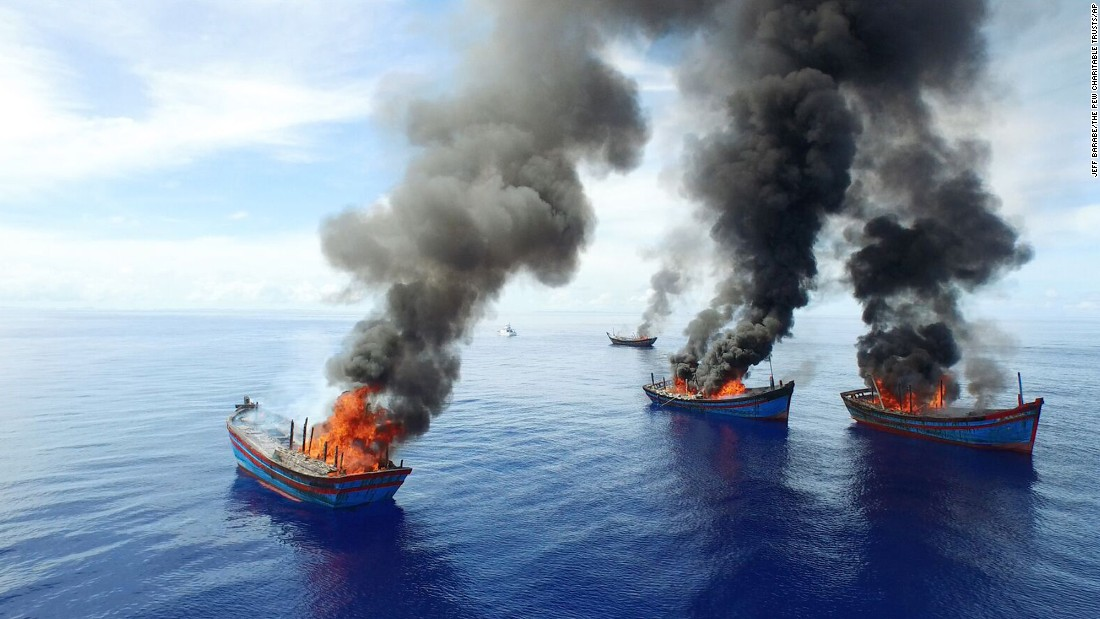 Columns of black smoke rise from four Vietnamese boats in the waters off Palau on Friday, June 12. Palau, a tiny Pacific nation fighting a tide of illegal fishing, set fire to the boats that it said were poaching sea cucumbers and other marine life.