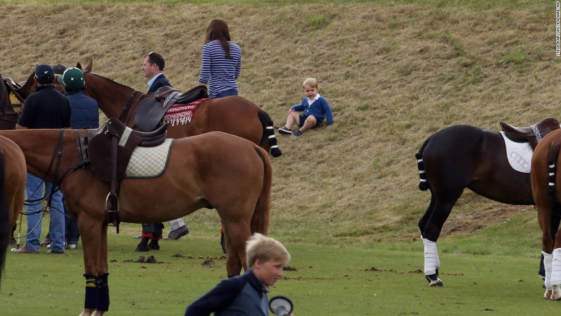 Britain's Prince George sits on a hill to watch a charity polo match in Tetbury, England, on Sunday, June 14. His mother, Catherine, Duchess of Cambridge, stands nearby. His father, Prince William, and his uncle Prince Harry were taking part in the event.