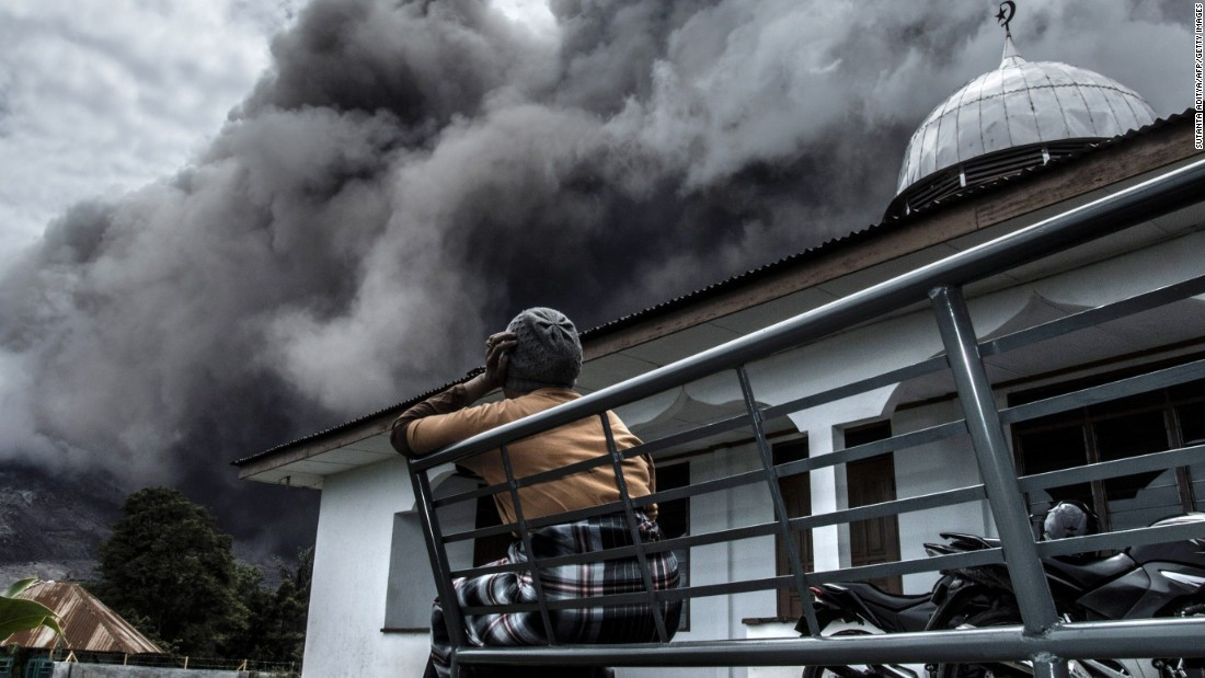 A woman in Karo, Indonesia, watches the Mount Sinabung volcano spew ash on Tuesday, June 16.