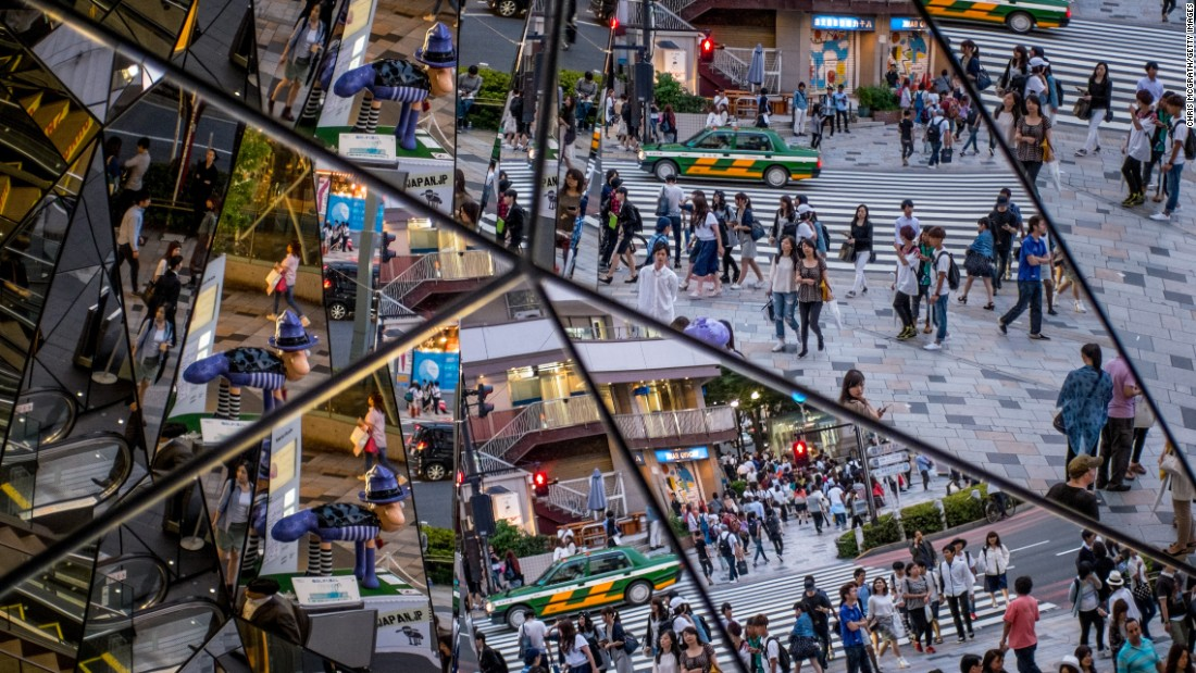 A busy intersection is reflected by a shopping-mall mirror in Tokyo on Thursday, June 18.