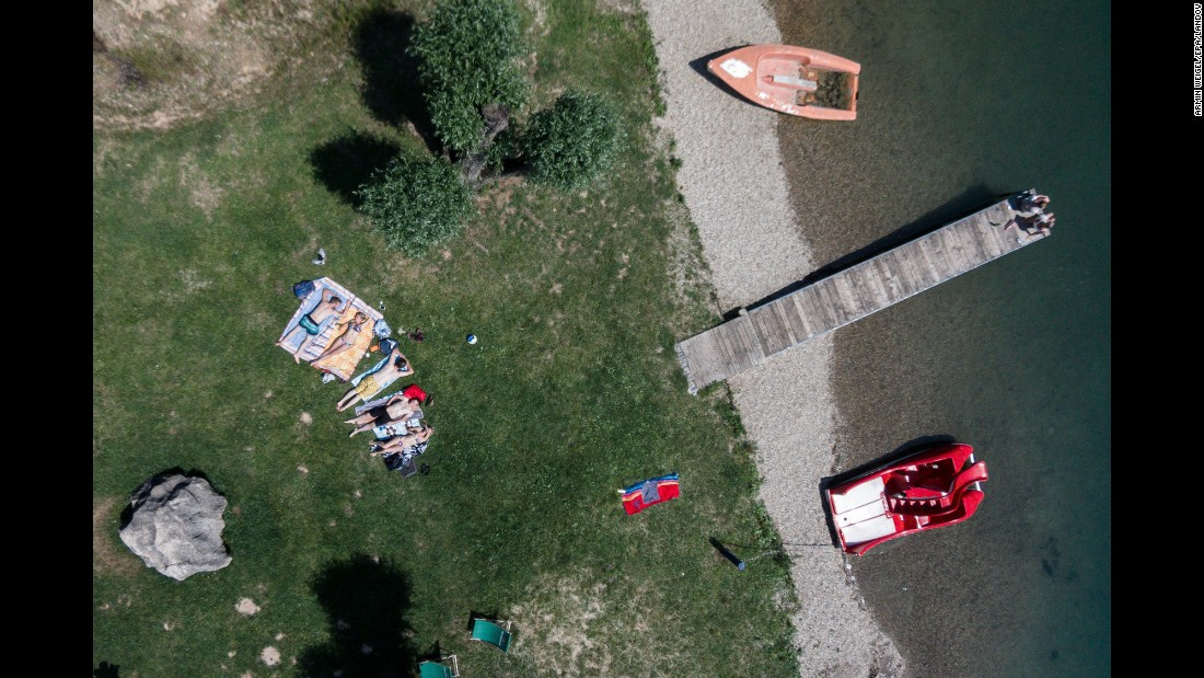 Sunbathers relax at a lake near Neutraubling, Germany, on Friday, June 12.