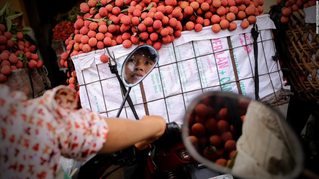 The reflection of a woman selling lychee is seen in her motorbike mirror Monday, June 15, in Luc Ngan, Vietnam.
