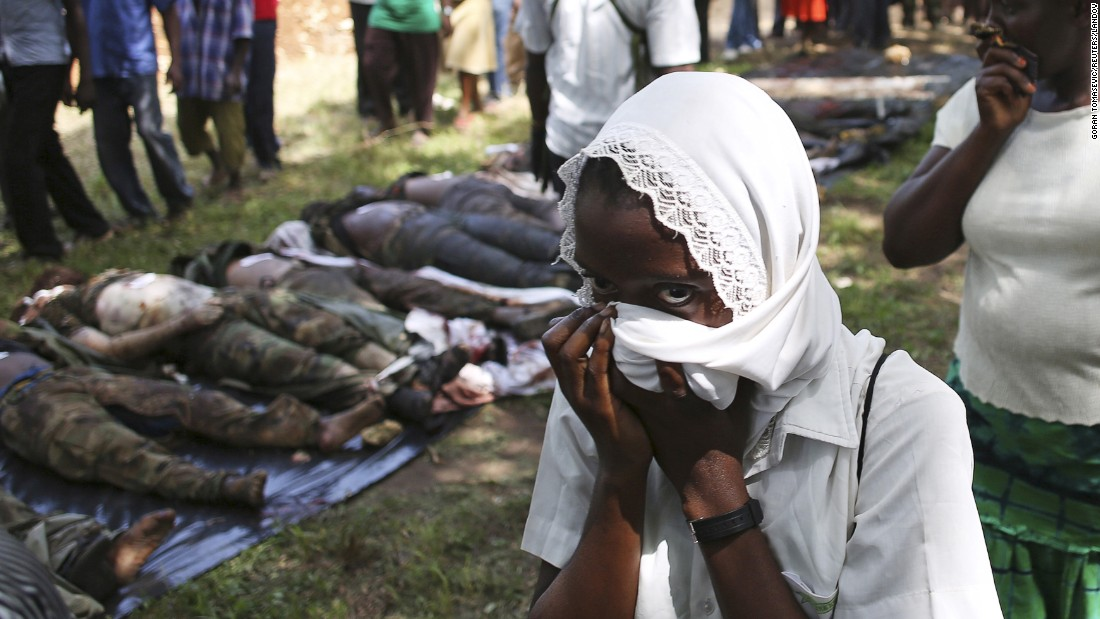 A woman passes by dead al-Shabaab fighters in Mpekatoni, Kenya, on Monday, June 15. Kenya's army said it had killed a regional commander from the Somali militant group.