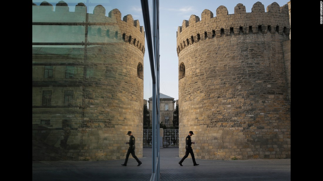 "A police officer walks past a fortress tower that is reflected in the glass pane of a modern building in Baku, Azerbaijan, on Wednesday, June 17. <a href=""http://www.cnn.com/2015/06/12/world/gallery/week-in-photos-0612/index.html"" target=""_blank"">See last week in 39 photos</a>"