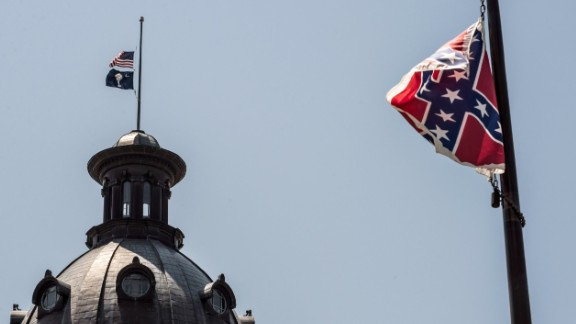 The South Carolina and American flags fly at half mast as the Confederate flag unfurls below at the Confederate Monument June 18, 2015 in Columbia, South Carolina. Legislators gathered Thursday morning to honor their co-worker Clementa Pinckney and the eight others killed Wednesday at Emanuel AME Church in Charleston, South Carolina.
