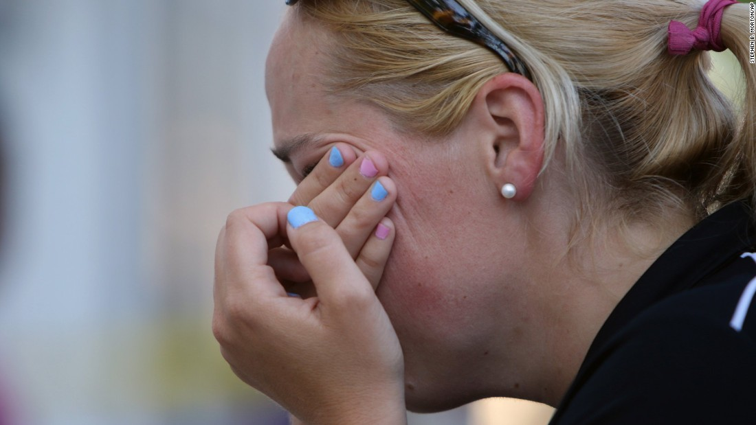 A woman wipes her eyes at a makeshift memorial near the Emanuel AME Church in Charleston on June 18.
