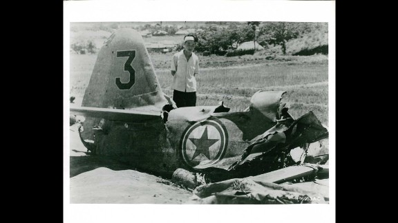 A South Korean inspects wreckage from a downed fighter plane north of Suwon in August 1950. Photo ID: *76953 A.C.