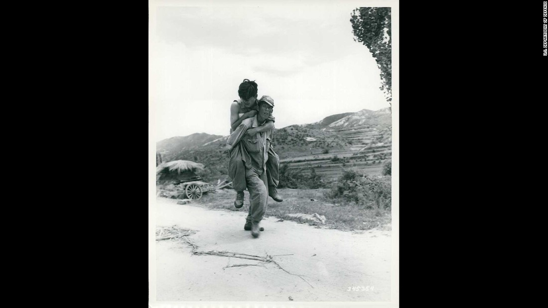 A South Korean soldier carries a wounded comrade in an unknown location in Korea in July 1950. Photo ID: SC 345354