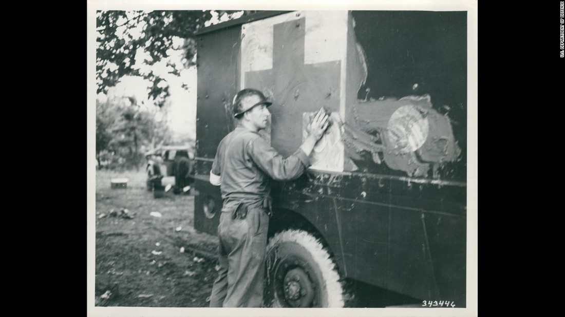An unidentified medical corpsman of the 24th Medical Battalion tries to camouflage an ambulance with mud in July 1950. Photo ID: SC 343446