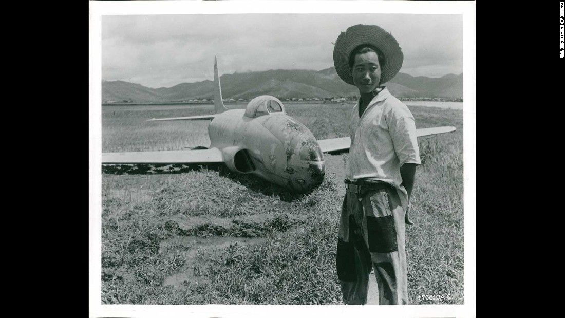 An unidentified farmer stands next to a battle-damaged fighter jet in a South Korean rice field in July 1950. Photo ID: *76810 A.C.