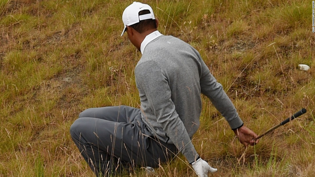 Down and out: Woods slips as he negotiates the rough on the 10th hole on his way to missing the halfway cut at the U.S. Open in June.