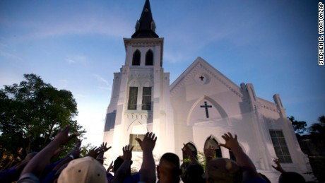 The men of Omega Psi Phi Fraternity Inc. lead a crowd of people in prayer outside the Emanuel AME Church, Friday, June 19, 2015.