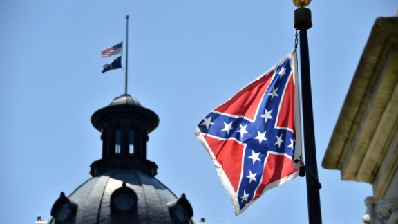 The South Carolina and American flags flying at half-staff behind the Confederate flag erected in front of the State Congress building in Columbia, South Carolina on June 19, 2015.