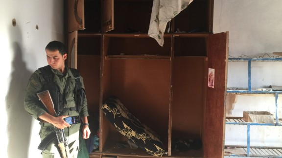 A Kurdish police officer looks around a former ISIS base.