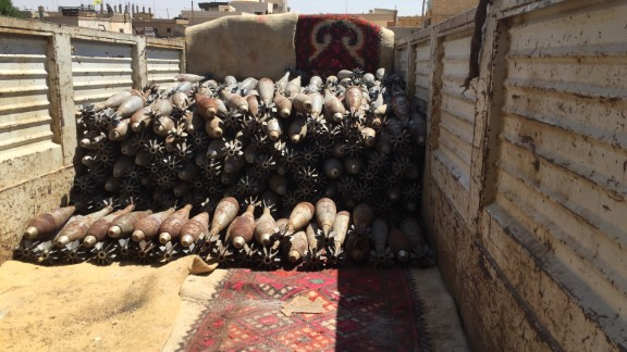 Stacked mortar rounds sit in the back of a flat-bed truck, ready to be moved.