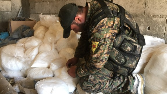 A YPG soldier looks through bags of sticky white powder, a low grade explosive that can be used to make car bombs.