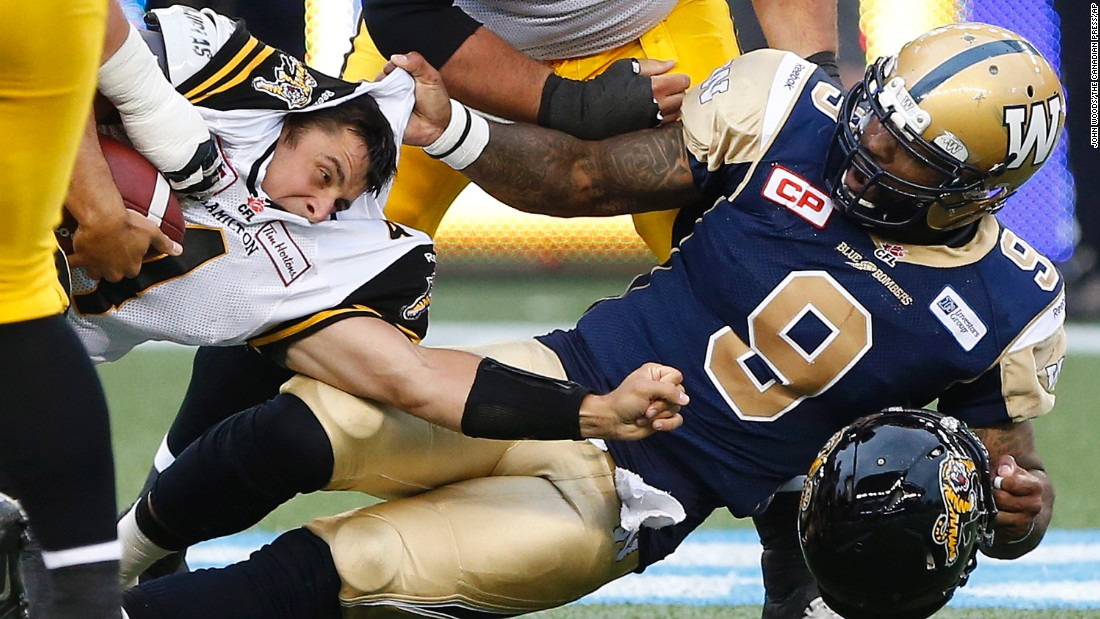 Winnipeg Blue Bombers' Thaddeus Gibson, No. 9, tackles Hamilton Tiger-Cats quarterback Zach Collaros, and later received a penalty for ripping off his helmet, during a Canadian Football League preseason game in Winnipeg, Manitoba, on Friday, June 19.