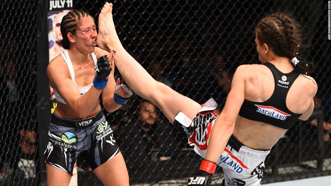 Joanna Jedrzejczyk of Poland lands a front kick against Jessica Penne of the United States in their women's strawweight championship bout during the UFC Fight Night event on Saturday, June 20, in Berlin.