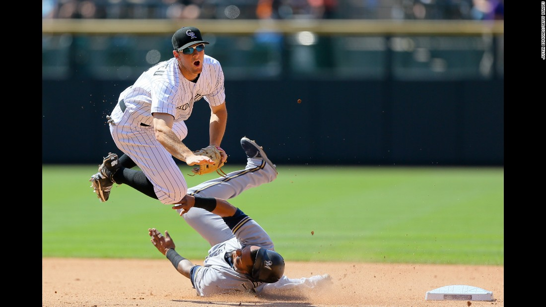 Second baseman D.J. LeMahieu of the Colorado Rockies is upended by Milwaukee Brewers' Martin Maldonado after throwing to first base to complete a double play at Coors Field on Saturday, June 20, in Denver. The Rockies defeated the Brewers 5-1.