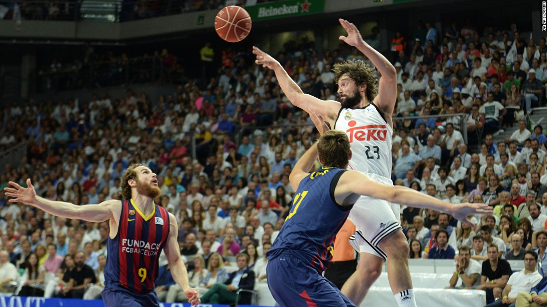 Players from RealMadrid and FCBarcelona vie for the ball during the first basketball match of the playoff finals of the Endesa League in Madrid on Friday, June 19.
