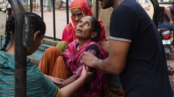 A man helps move a heat wave victim to a Karachi hospital on Monday, June 22.