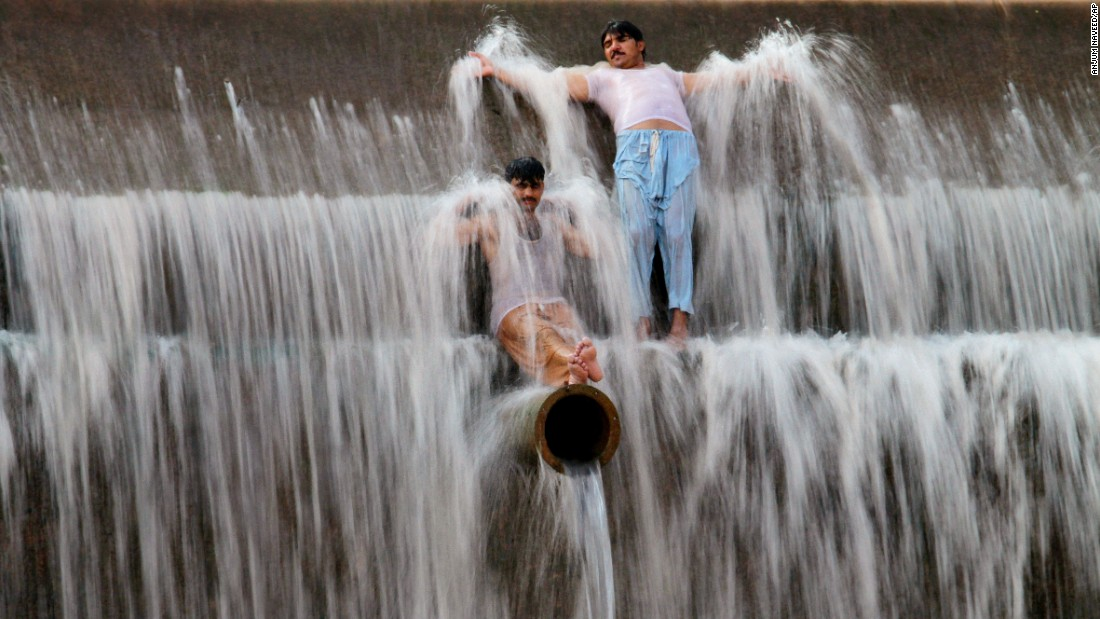 Pakistanis cool off at a river outside Islamabad on Sunday, June 21.