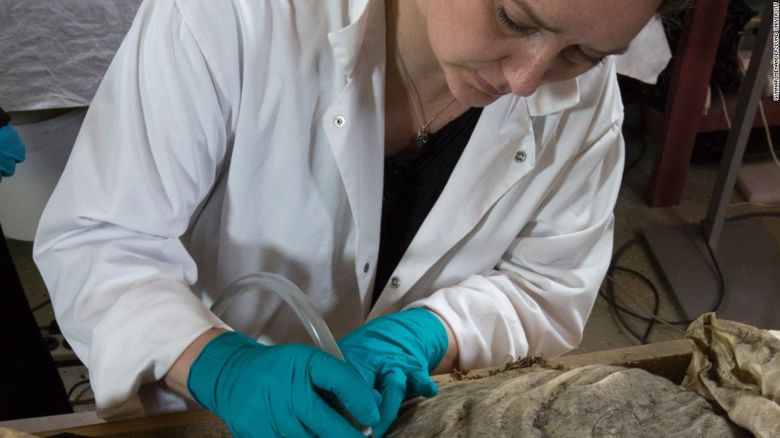 Researchers plan to carry out a DNA test of the fetus found at Winstrup's feet to establish if the two are related. Here museum conservator  Lovisa Dal vacuums the bishop's remains.