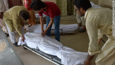 Pakistani volunteers and relatives prepare to shift the bodies of heatwave victims into the cold storage of the Edhi morgue in Karachi on June 22, 2015.
