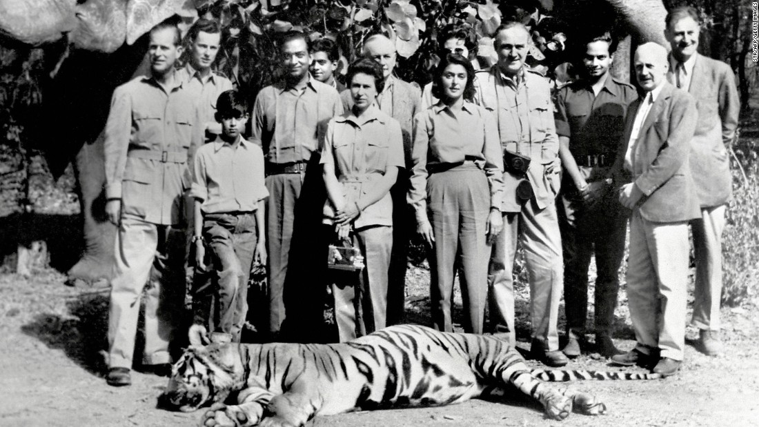 In 1961, Queen Elizabeth II and Prince Philip visited India. Here they are standing with the Maharaja (fourth from the left) and Maharani (fifth from the right) of Jaipur, following a tiger shoot in the Rajasthani city of Jaipur. Despite the fact that she's on a tiger hunt, the Queen has not forgotten her handbag.