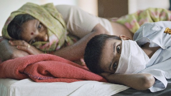 A patient with plague symptoms, foreground, awaits test results with his mother at New Delhi