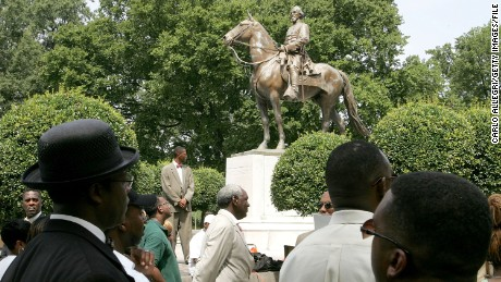 MEMPHIS, TN - AUGUST 13: Protesters attend a rally protesting against the name of Nathan Bedford Forrest Park in front of a statue bearing his likeness August 13, 2005 in Memphis, Tennessee. Nathan Bedford Forrest was a Civil War General who led troops against the north. Forrest was originally buried in Elmwood Cemetery in Memphis. In 1905 Confederate veterans arranged to move his remains and those of his wife Mary to a new site, named Forrest Park, which is adorned with a statue of him riding a horse. (Photo by Carlo Allegri/Getty Images)