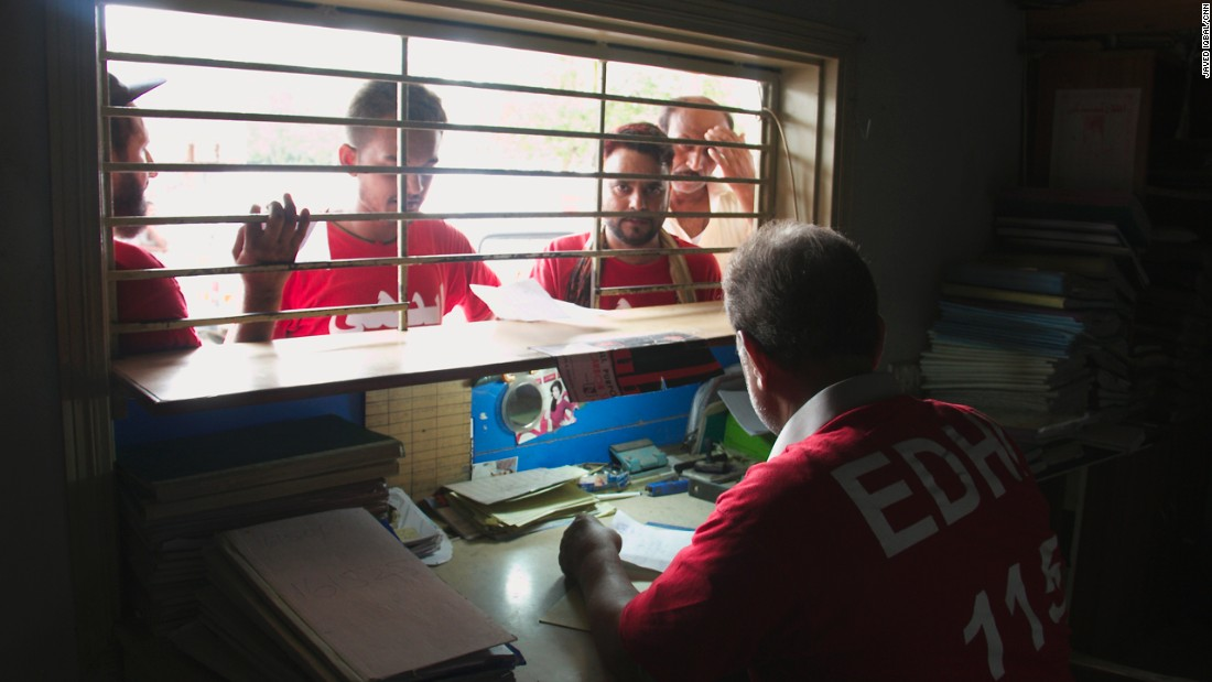 Morgue workers, in red, register bodies at the morgue, while a civilian searching for relatives stands patiently behind.