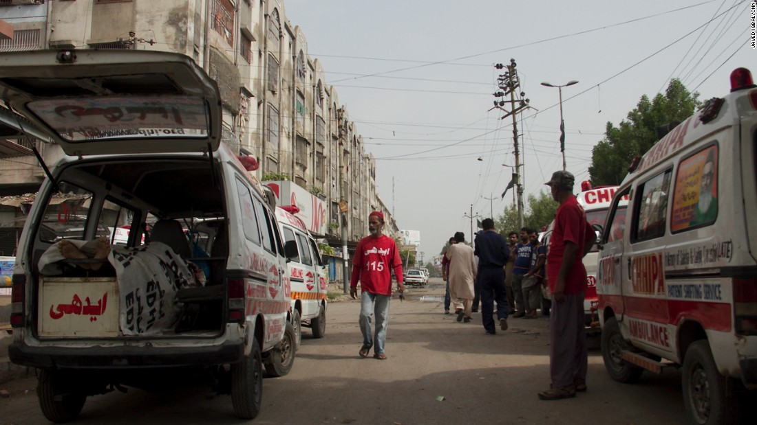 A morgue worker, in red, walks between ambulances outside the Edhi morgue. The ambulances are loaded with corpses.