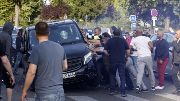 Demonstrators try to turn over a car at Porte Maillot in Paris on June 25.
