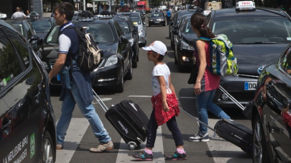 Tourists walk past taxis blocking an avenue in Paris on June 25. The protests slowed road access to airports near Paris.