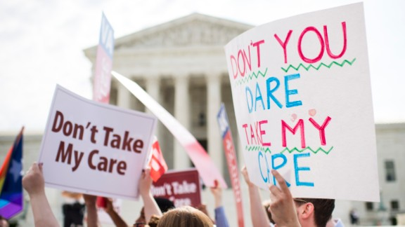 UNITED STATES - JUNE 25: Affordable Care Act supporters hold up signs outside the Supreme Court as they wait for the court