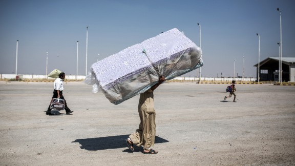 A refugee carries mattresses as he re-enters Syria from Turkey on June 22, 2015, after Kurdish People