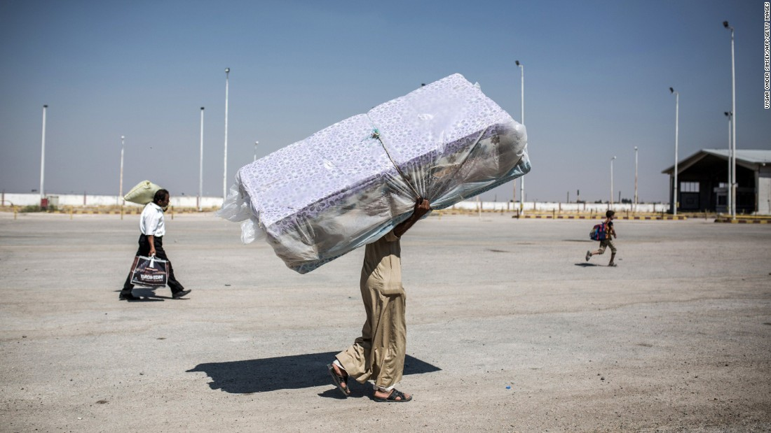 A refugee carries mattresses as he re-enters Syria from Turkey on June 22, 2015, after Kurdish People's Protection Units regained control of the area around Tal Abyad, Syria, from ISIS.
