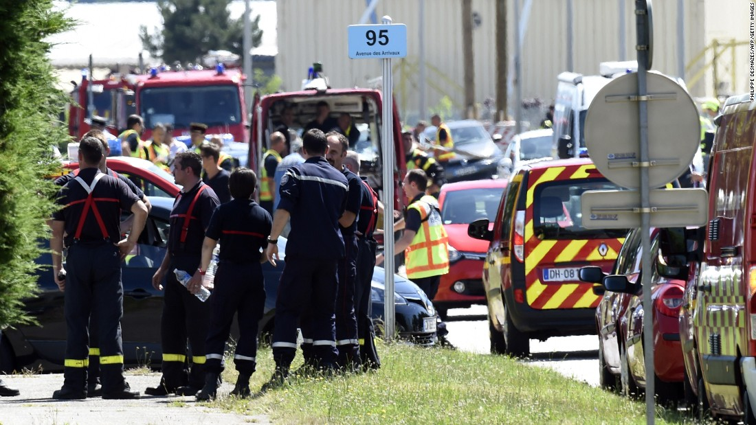 Police and firefighters gather at the entrance of Air Products & Chemicals, a gas factory near Lyon, France, on Friday, June 26, after a terror attack. One person has been beheaded and two people injured, French President François Hollande said Friday. A suspect has been arrested, he said.