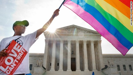 Carlos McKnight of Washington, waves a flag in support of gay marriage outside of the Supreme Court in Washington, Friday June 26, 2015. A major opinion on gay marriage is among the remaining to be released before the term ends at the end of June. (AP Photo/Jacquelyn Martin)