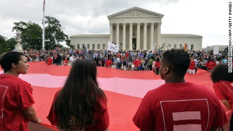 People wave a giant equality flag as they celebrate outside the Supreme Court on June 26.