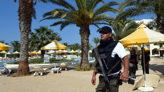 A Tunisian security member stands next to a swimming pool at the hotel.