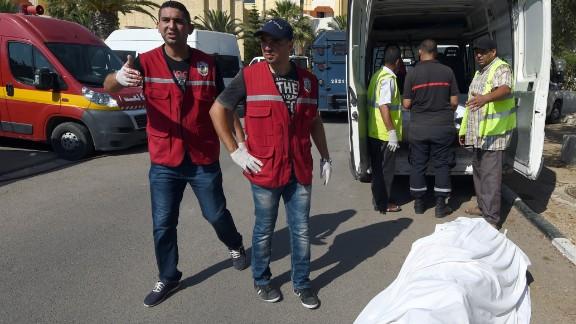 Tunisian medics stand near a tourist