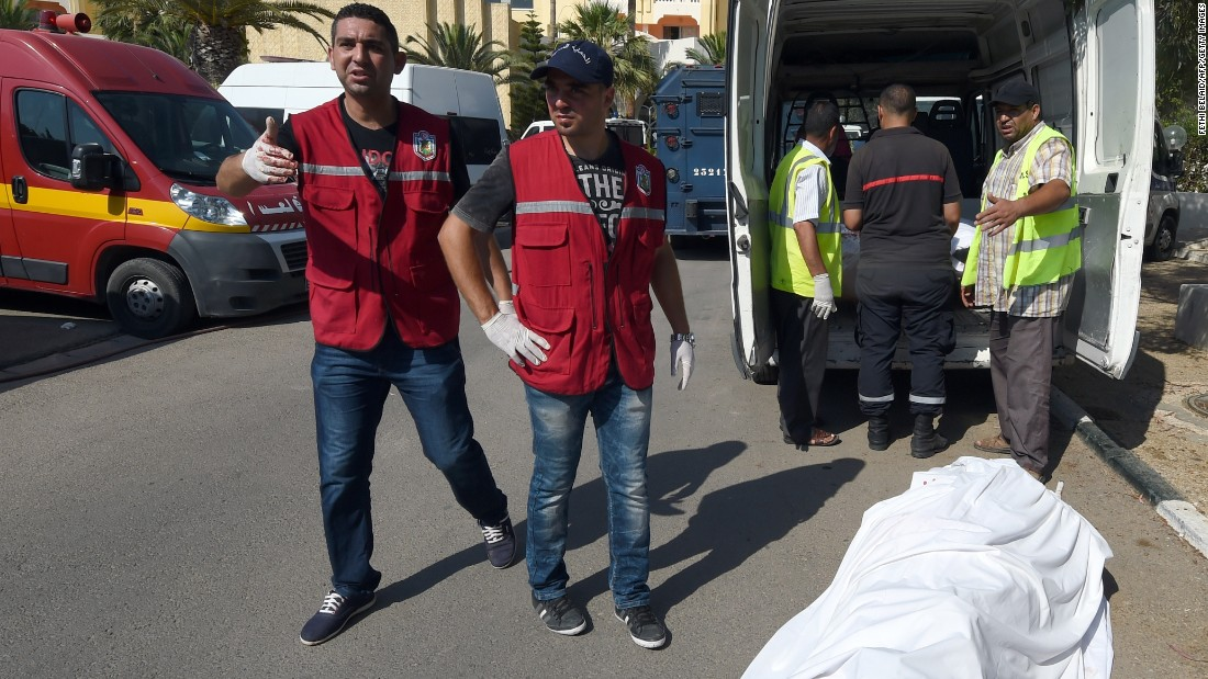 Tunisian medics stand near a tourist's body.
