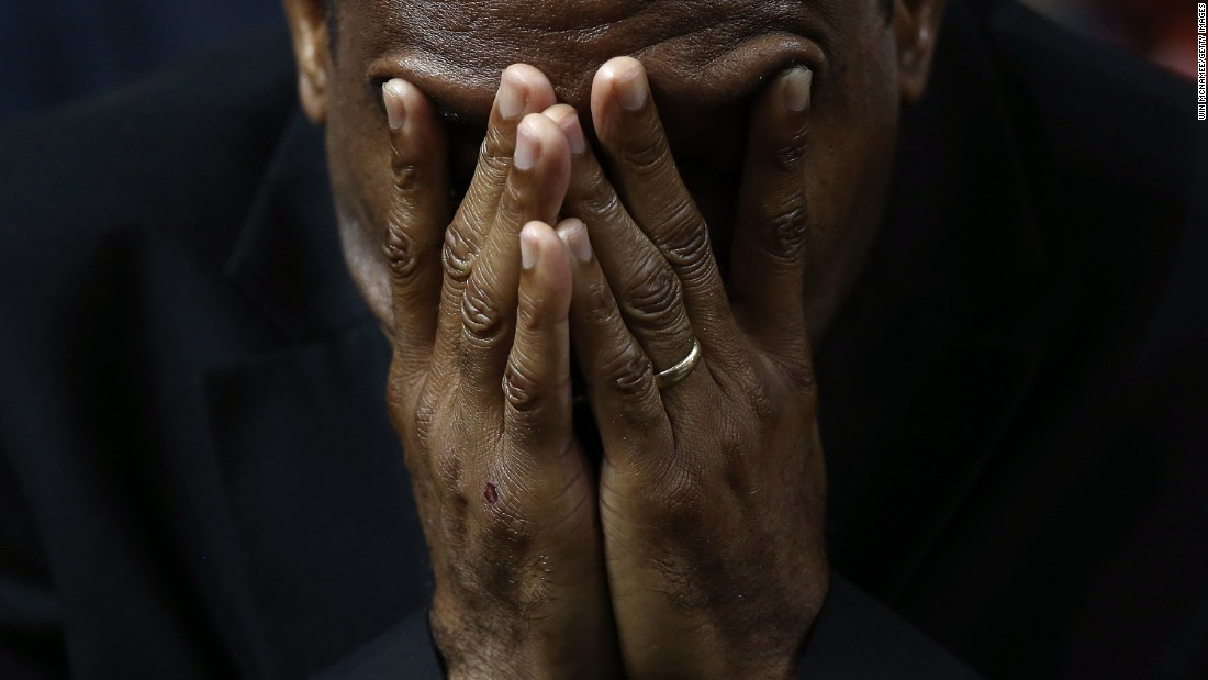 A mourner bows his head in prayer.