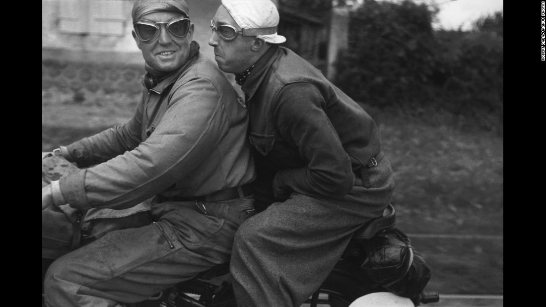 Photographers like Capa had to find ways to keep up with the Tour cyclists. A favored method was hitching a ride on a motorcycle. Here, Capa shows a press reporter and his motorcycle driver.