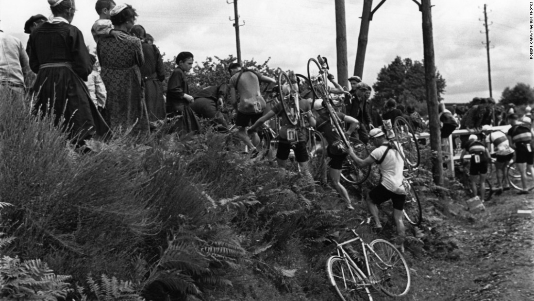 When the route was changed during the 1939 Tour, Capa was there to show the cyclists carrying their bikes over some brush -- and to note the curious eyes of local residents.